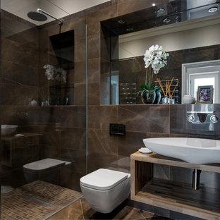 Foto di una stanza da bagno con doccia contemporanea di medie dimensioni con piastrelle marroni, piastrelle in ceramica, pavimento con piastrelle in ceramica, pavimento marrone, doccia aperta, WC sospeso, lavabo a bacinella, nessun'anta, doccia a filo pavimento e top marrone