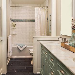 Modelo de cuarto de baño clásico, de tamaño medio, con armarios tipo mueble, puertas de armario verdes, bañera empotrada, ducha doble, sanitario de dos piezas, baldosas y/o azulejos blancos, baldosas y/o azulejos de cemento, paredes beige, suelo de pizarra, lavabo bajoencimera y encimera de mármol