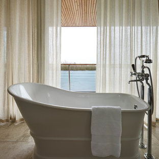 This is an example of a contemporary bathroom in Gloucestershire with a freestanding bath and beige floors.