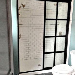 Mittelgroßes Industrial Duschbad mit offenen Schränken, gelben Schränken, Duschnische, Wandtoilette mit Spülkasten, grauen Fliesen, weißen Fliesen, Metrofliesen, grüner Wandfarbe, Keramikboden und Waschtischkonsole in Sonstige