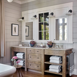 Modelo de cuarto de baño rural con armarios tipo mueble, puertas de armario de madera oscura, paredes grises, suelo de madera en tonos medios, lavabo bajoencimera, suelo marrón y encimeras grises