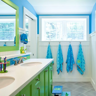 This is an example of a coastal family bathroom in Portland Maine with green cabinets, multi-coloured tiles, ceramic flooring, a submerged sink, recessed-panel cabinets, stone tiles and blue walls.