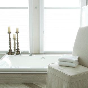 Удачное сочетание для дизайна помещения: большая главная ванная комната в классическом стиле с фасадами с утопленной филенкой, белыми фасадами, накладной ванной, душем в нише, бежевой плиткой, плиткой из травертина, бежевыми стенами, полом из керамогранита, врезной раковиной, столешницей из оникса, бежевым полом и душем с распашными дверями - самое интересное для вас