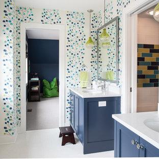 Cette image montre une salle de bain traditionnelle avec un lavabo encastré, un placard à porte shaker, des portes de placard bleues, un mur multicolore et un sol en carrelage de terre cuite.