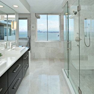 Example of a large minimalist master white tile and marble tile marble floor and white floor bathroom design in Cleveland with flat-panel cabinets, black cabinets, white walls, a vessel sink, solid surface countertops and a hinged shower door