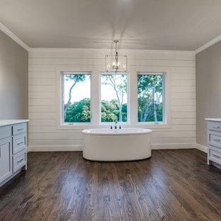 Ispirazione per una grande stanza da bagno padronale country con ante in stile shaker, ante grigie, vasca da incasso, pareti grigie, lavabo sottopiano, top in marmo e parquet scuro