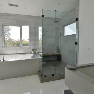 Immagine di una grande stanza da bagno padronale minimalista con nessun'anta, ante nere, vasca idromassaggio, doccia alcova, pareti grigie, lavabo rettangolare e top in superficie solida
