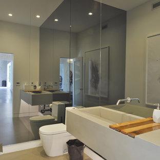 На фото: ванная комната среднего размера в стиле модернизм с унитазом-моноблоком, серыми стенами, бетонным полом, раковиной с несколькими смесителями и душевой кабиной с