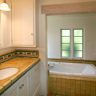 This is an example of a mediterranean ensuite bathroom in San Francisco with a submerged sink, beaded cabinets, white cabinets, tiled worktops, a built-in bath, yellow tiles, ceramic tiles and white walls.