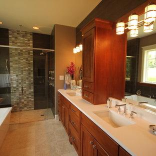 Modelo de cuarto de baño principal, de estilo americano, grande, con lavabo bajoencimera, armarios tipo mueble, puertas de armario de madera oscura, encimera de cuarzo compacto, bañera exenta, ducha a ras de suelo, sanitario de una pieza, baldosas y/o azulejos de cerámica, paredes beige y suelo de baldosas de cerámica