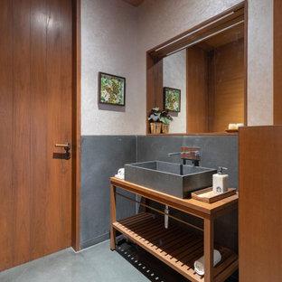 Foto på ett mellanstort funkis brun badrum med dusch, med skåp i mellenmörkt trä, grå kakel, ett fristående handfat, träbänkskiva och grått golv