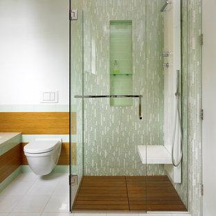 Esempio di una stanza da bagno design con doccia a filo pavimento, WC sospeso, piastrelle verdi, piastrelle di vetro, nicchia e panca da doccia