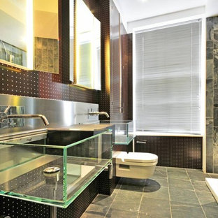 This is an example of a medium sized urban bathroom in London with a wall mounted toilet, a wall-mounted sink, grey floors, a corner shower, grey tiles and black walls.