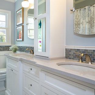 Exempel på ett litet klassiskt badrum, med ett undermonterad handfat, vita skåp, bänkskiva i kvarts, ett badkar i en alkov, en dusch/badkar-kombination, en toalettstol med separat cisternkåpa, vit kakel, porslinskakel, grå väggar, klinkergolv i porslin och luckor med infälld panel