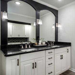 Imagen de cuarto de baño principal, actual, de tamaño medio, con puertas de armario blancas, paredes grises, suelo vinílico, lavabo bajoencimera, encimera de granito, suelo marrón y encimeras negras