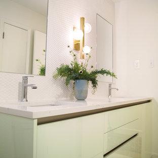 Esempio di una stanza da bagno con doccia minimalista con ante lisce, ante verdi, doccia alcova, pistrelle in bianco e nero, piastrelle in ceramica, pareti bianche, pavimento in laminato, lavabo da incasso, top in granito, pavimento bianco e porta doccia a battente