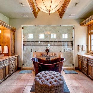 Immagine di un'ampia stanza da bagno padronale mediterranea con lavabo sottopiano, ante in legno bruno, vasca freestanding, piastrelle beige, pareti beige, ante a filo, doccia doppia, pavimento in travertino, pavimento marrone, porta doccia a battente e top beige
