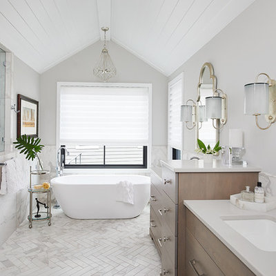 Example of a transitional white floor freestanding bathtub design in Grand Rapids with flat-panel cabinets, dark wood cabinets, gray walls, an undermount sink and gray countertops