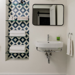 Cette image montre une petite salle de bain minimaliste avec un WC à poser, un carrelage bleu, des carreaux de béton, un mur blanc, un sol en carreaux de ciment, un lavabo suspendu, un sol bleu et une cabine de douche à porte battante.