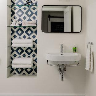 Cette image montre une petit salle de bain minimaliste avec un WC à poser, un carrelage bleu, des carreaux de béton, un mur blanc, un sol en carreaux de ciment, un lavabo suspendu, un sol bleu et une cabine de douche à porte battante.