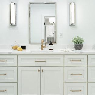 Modelo de cuarto de baño principal, actual, de tamaño medio, con armarios estilo shaker, puertas de armario azules, suelo de mármol, lavabo bajoencimera, encimera de cuarzo compacto, suelo amarillo y encimeras blancas