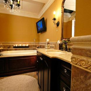 Foto de cuarto de baño principal, mediterráneo, grande, con armarios con paneles con relieve, puertas de armario negras, bañera empotrada, ducha empotrada, baldosas y/o azulejos marrones, baldosas y/o azulejos de piedra, paredes marrones y lavabo bajoencimera
