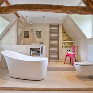 Farmhouse ensuite bathroom in Oxfordshire with flat-panel cabinets, grey cabinets, a freestanding bath, an alcove shower, a wall mounted toilet, beige tiles, beige walls, beige floors and an open shower.