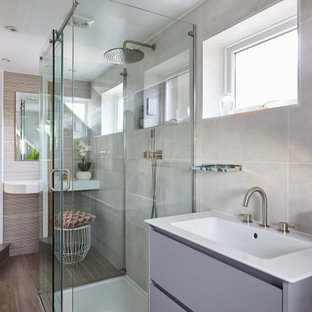 Inspiration for a medium sized contemporary shower room bathroom in London with flat-panel cabinets, grey cabinets, a corner shower, grey tiles, an integrated sink, grey floors, a hinged door, white worktops, a single sink and a built in vanity unit.