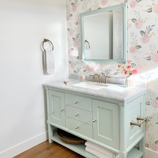 Esempio di una stanza da bagno country con ante turchesi, vasca da incasso, vasca/doccia, piastrelle bianche, piastrelle di marmo, pareti multicolore, pavimento in laminato, lavabo sottopiano, top in marmo, pavimento marrone, doccia con tenda e top bianco