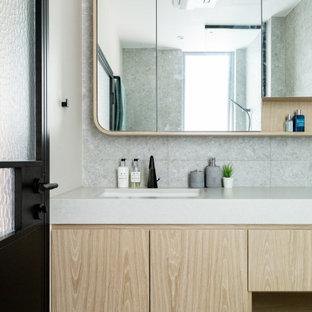 Diseño de cuarto de baño moderno, pequeño, con armarios con paneles lisos, bañera encastrada, bidé, baldosas y/o azulejos grises, baldosas y/o azulejos de piedra, paredes grises, suelo de baldosas de cerámica, lavabo encastrado, encimera de piedra caliza, suelo gris y encimeras blancas