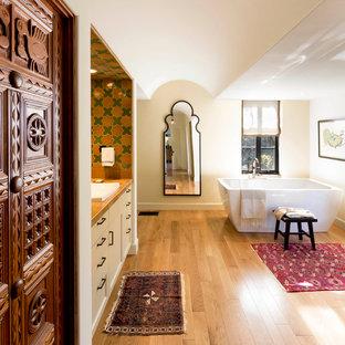 Diseño de cuarto de baño principal, mediterráneo, grande, con armarios estilo shaker, puertas de armario beige, bañera exenta, ducha empotrada, sanitario de dos piezas, baldosas y/o azulejos multicolor, baldosas y/o azulejos de porcelana, paredes beige, lavabo encastrado, encimera de azulejos y suelo de madera en tonos medios