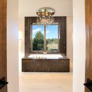 Inspiration pour une grand salle de bain principale sud-ouest américain avec une baignoire encastrée, un carrelage gris, des carreaux de béton, un mur gris et un sol beige.
