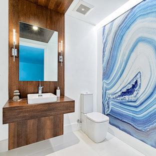 Imagen de cuarto de baño con ducha, contemporáneo, de tamaño medio, con sanitario de dos piezas, lavabo sobreencimera, encimera de madera, paredes azules, armarios abiertos, puertas de armario de madera oscura y suelo de baldosas de porcelana
