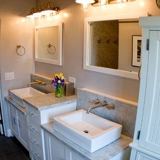 Diseño de cuarto de baño principal, de estilo americano, pequeño, con lavabo sobreencimera, armarios estilo shaker, puertas de armario blancas, encimera de granito, ducha empotrada, baldosas y/o azulejos grises, paredes grises, suelo de baldosas de porcelana y suelo marrón