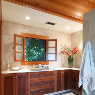 Immagine di una grande stanza da bagno padronale tropicale con ante con riquadro incassato, ante in legno scuro, piastrelle beige, lavabo sottopiano, WC a due pezzi, piastrelle in pietra, top in marmo, pareti beige e pavimento con piastrelle in ceramica