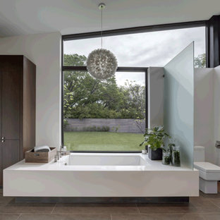 Doorless shower - huge modern master ceramic tile and brown floor doorless shower idea in Dallas with flat-panel cabinets, medium tone wood cabinets, an undermount tub, a one-piece toilet, white walls, quartz countertops, a hinged shower door and white countertops