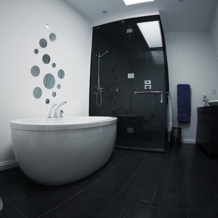 This is an example of a mid-sized contemporary master bathroom in Toronto with flat-panel cabinets, black cabinets, a freestanding tub, a corner shower, white walls, a two-piece toilet, porcelain floors, a vessel sink, mirror tile, black floor and a hinged shower door.