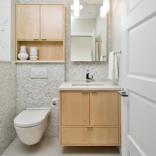 Example of a small trendy white tile and stone tile porcelain floor bathroom design in Ottawa with an undermount sink, flat-panel cabinets, light wood cabinets, engineered quartz countertops, a wall-mount toilet and gray walls