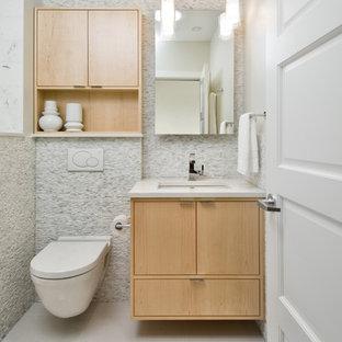 Новые идеи обустройства дома: маленькая ванная комната в современном стиле с врезной раковиной, плоскими фасадами, светлыми деревянными фасадами, столешницей из искусственного кварца, инсталляцией, белой плиткой, каменной плиткой, серыми стенами и полом из керамогранита