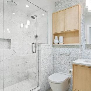 Ejemplo de cuarto de baño actual, pequeño, con lavabo bajoencimera, armarios con paneles lisos, puertas de armario de madera clara, encimera de cuarzo compacto, sanitario de pared, baldosas y/o azulejos blancos, baldosas y/o azulejos de piedra, paredes grises y suelo de baldosas de porcelana