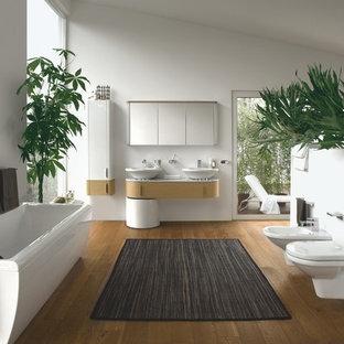 Diseño de cuarto de baño principal, actual, grande, con armarios con paneles lisos, puertas de armario de madera clara, bañera encastrada, combinación de ducha y bañera, sanitario de pared, baldosas y/o azulejos blancos, paredes blancas, lavabo sobreencimera, encimera de mármol y suelo de bambú