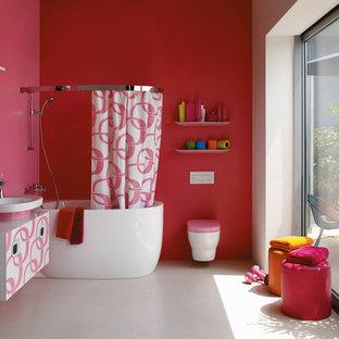 Ispirazione per una stanza da bagno padronale design di medie dimensioni con ante lisce, ante bianche, vasca da incasso, vasca/doccia, WC sospeso, pareti rosa, pavimento in cemento, lavabo a bacinella e top in superficie solida