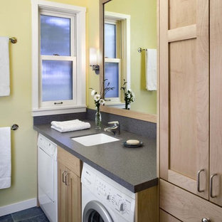 This is an example of a country bathroom in San Francisco with light wood cabinets, slate floors, yellow walls, black floor and a laundry.