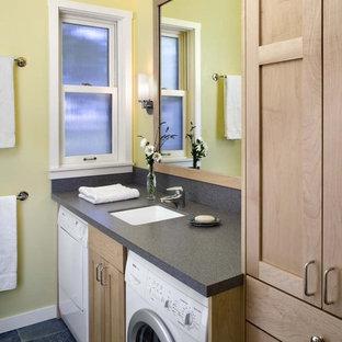 Réalisation d'une salle de bain chalet avec des portes de placard en bois clair, un sol en ardoise, un mur jaune, un sol noir et buanderie.