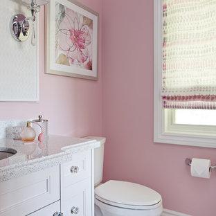 Inredning av ett klassiskt mellanstort badrum för barn, med ett undermonterad handfat, luckor med profilerade fronter, vita skåp, bänkskiva i kvarts, en toalettstol med hel cisternkåpa, vit kakel, porslinskakel, rosa väggar och klinkergolv i porslin
