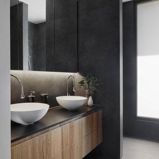 メルボルンの中くらいのコンテンポラリースタイルのおしゃれなマスターバスルーム (フラットパネル扉のキャビネット、中間色木目調キャビネット、黒いタイル、セラミックタイル、セラミックタイルの床、ベッセル式洗面器、クオーツストーンの洗面台、黒い洗面カウンター、グレーの床、洗面台2つ、フローティング洗面台) の写真