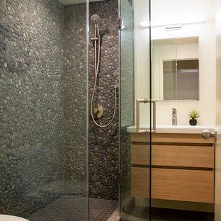 Ispirazione per una piccola stanza da bagno etnica con ante lisce, ante in legno scuro, piastrelle grigie, piastrelle di ciottoli, pareti bianche, pavimento in gres porcellanato, lavabo integrato, top in superficie solida, pavimento grigio, porta doccia a battente e top giallo