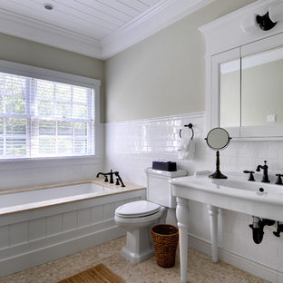 Alcove shower - large traditional master subway tile and white tile limestone floor alcove shower idea in Manchester with a console sink, open cabinets, an undermount tub and beige walls