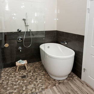 Example of a mid-sized zen master beige tile and porcelain tile porcelain tile and beige floor bathroom design in DC Metro with shaker cabinets, gray cabinets, a two-piece toilet, beige walls, an undermount sink, quartz countertops and a hinged shower door