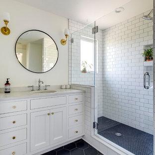 ポートランドの大きいトラディショナルスタイルのおしゃれな浴室 (落し込みパネル扉のキャビネット、白いキャビネット、アルコーブ型シャワー、白いタイル、サブウェイタイル、ベージュの壁、磁器タイルの床、アンダーカウンター洗面器、珪岩の洗面台、黒い床、開き戸のシャワー、白い洗面カウンター) の写真